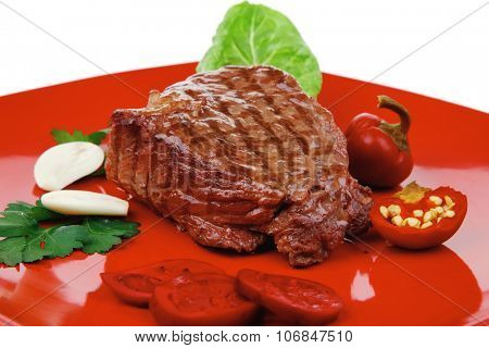 barbecued meat : beef ( lamb ) garnished with green lettuce and red chili hot pepper on red plate isolated over white background