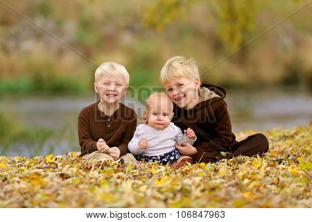 Swee Happy Children Sitting In Fallen Leaves