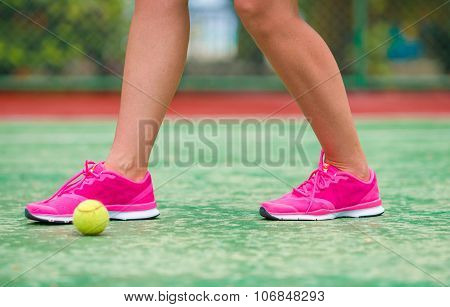 Closeup of sneakers near the tennis racquet and ball