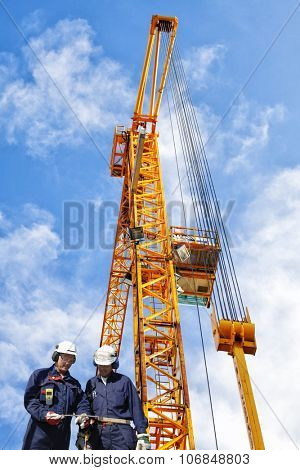 two building workers and large construction crane
