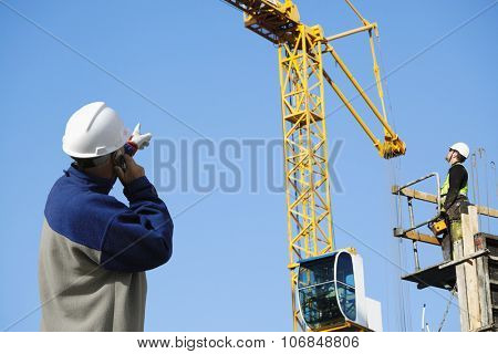 site foreman directing remote controled construction-crane