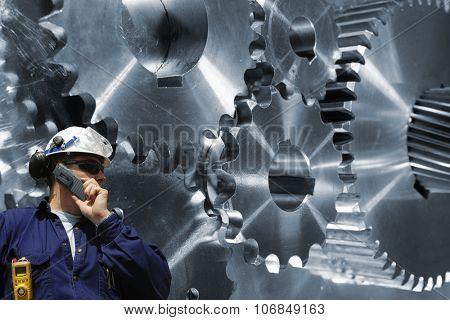 engineer, mechanic with large cogwheels and gears machinery