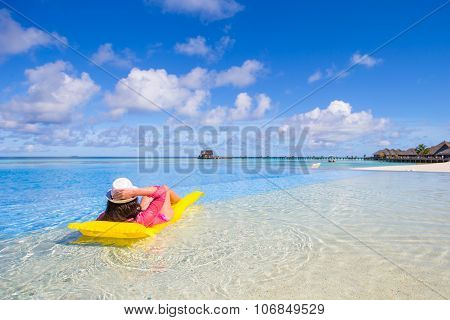 Young happy woman relaxing with air mattress on the beach