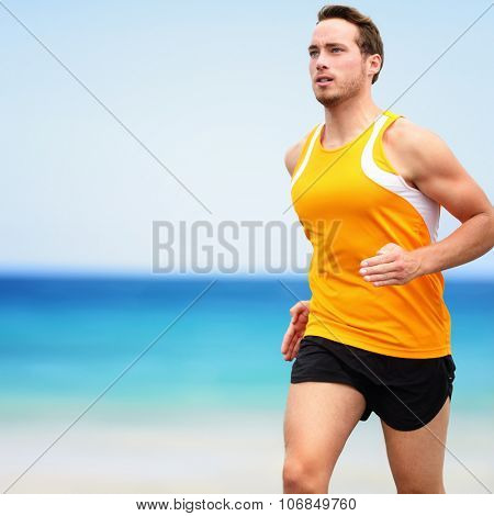 Fit young man in sports clothing running on beach. Determined male runner is exercising against ocean and sky. He is representing his healthy lifestyle.
