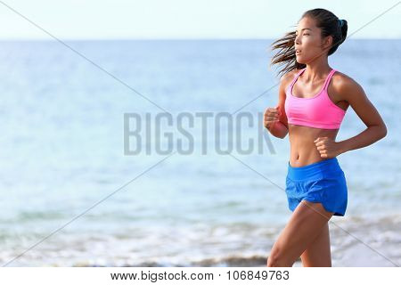 Determined woman jogging on beach. Fit young female is in sports clothing. Jogger is exercising against ocean during sunny day.