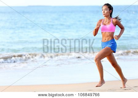 Running Determined young woman runner jogging on beach. Full length of fit female is in sports clothing. Jogger is exercising at sea shore during sunny day.
