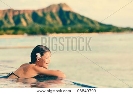 Smiling beautiful woman relaxing in infinity swimming pool. Side view of happy female looking at ocean view on sunny day. Young tourist is enjoying summer vacation against mountain.