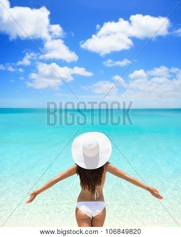 Beach woman standing with arms outstretched against turquoise sea and blue sky. Rear view of female wearing white sunhat and bikini. Carefree tourist is enjoying vacation at beach.