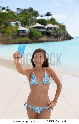 Beach vacation travel woman making smart phone selfie in bikini having fun sharing on social media. Self portrait photo with smartphone on beach. Happy mixed race Caucasian / Asian Chinese woman.