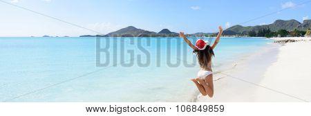 Woman with arms outstretched jumping at beach. Rear view of female is wearing Santa hat and bikini. Carefree tourist is enjoying Christmas vacation on sunny day.