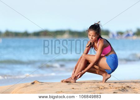 Young jogger running suffering from ankle pain injury on beach. Full length of female runner in sportswear. Woman is holding her twisted leg while crouching on sea shore.