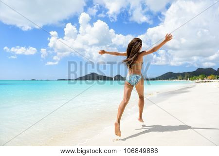 Travel, beach and vacation holidays concept with bikini girl happy running full of joy and aspiration on pristine beautiful Caribbean beach with turquoise water. Woman in bikini having fun.