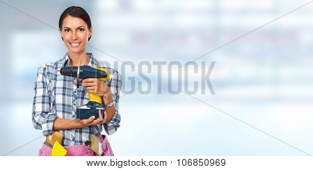 Young woman with a drill. House renovation blue background.