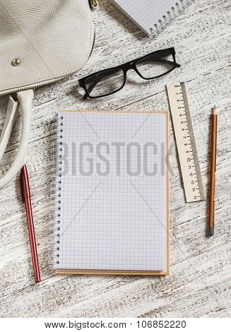 Open A Blank White Notebook, Pen, Women's Bag, Ruler, Pencil  On The White Desk