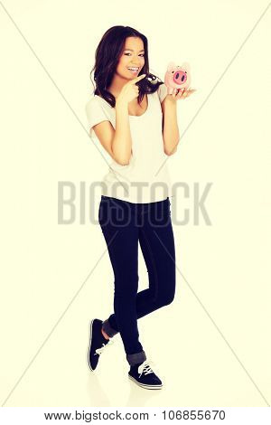 Happy african woman pointing on piggybank.