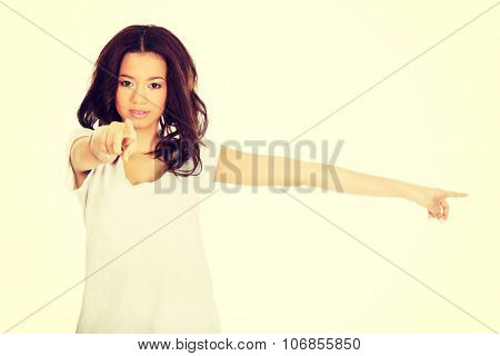 Beautiful serious woman pointing on you and aside.