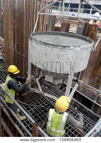 A group of construction workers pouring concrete slurry into pile cap formwork