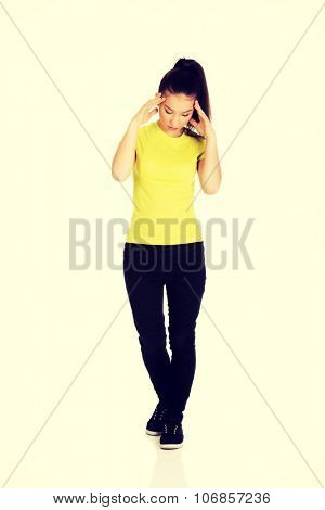 Teen woman with headache holding her hand to the head.