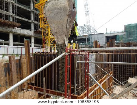 Construction workers pouring concrete slurry into reinforcement concrete wall formwork