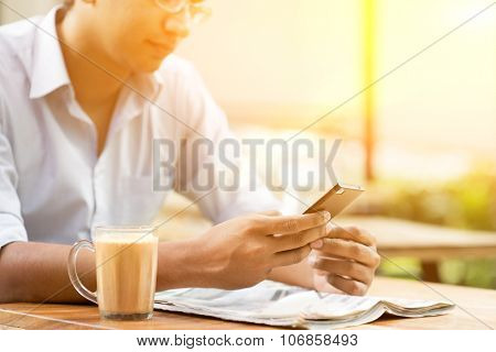 Asian Indian businessman using smartphone at cafeteria, beautiful sunlight background.