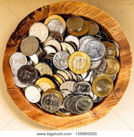 Savings concept ~ Coins kept on a plate on a plain background