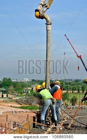Construction Workers Using Concrete Hose from Concrete Pump