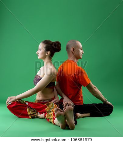 Paired yoga training in studio, on green backdrop