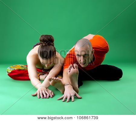Paired yoga training. Instructor looking at camera