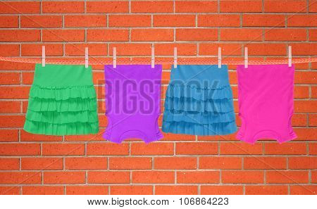 Laundry Line With Clothes Over Orange Brick Wall Background