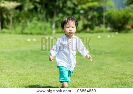 Little boy walking though at park