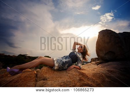 Brunette Girl In Short Grey Frock Sits On Rock Against Sky