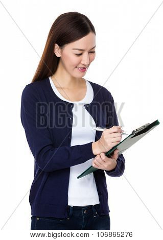 Asian Young Woman take note on clipboard