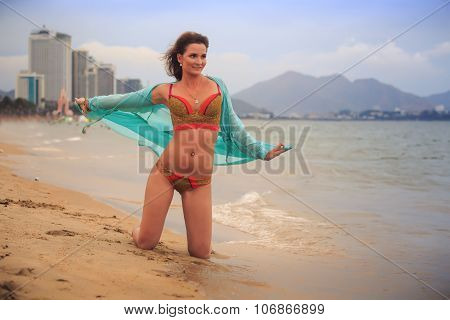 Girl In Bikini Transparent Frock Stands On Knees On Wet Sand
