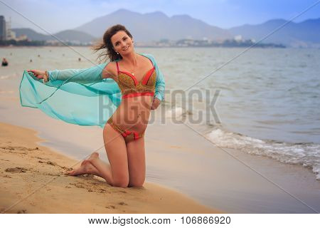 Closeup Brunette Girl In Bikini Stands On Knees On Wet Sand