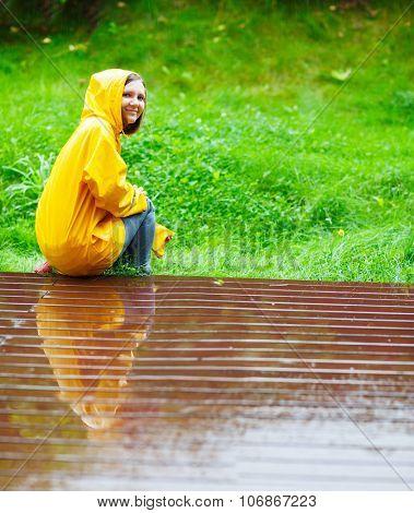 Happy young woman in yellow raincoat under rain