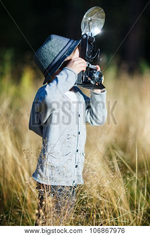 Stylish small boy with retro camera photographing outdoors on sunny autumn day