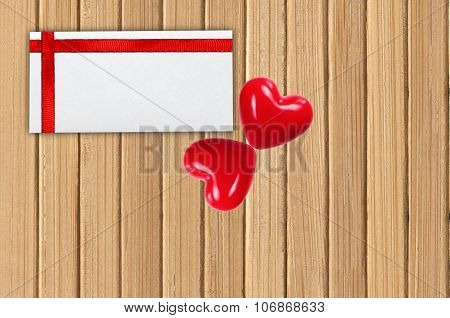 Greeting Card With Red Ribbon And Two Red Hearts On Wooden Planks Background