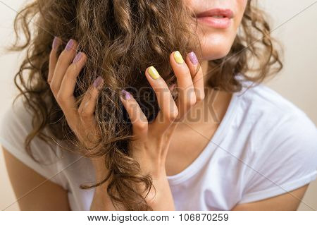 Female Hands With A Bright Purple And Yellow Manicure Holding Brown Curly Hair