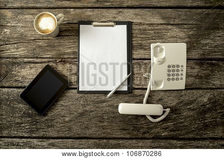 Top View Of Digital Tablet, Empy Sheet Of Paper On Black Clipboard, Pen, Landline Telephone With Han