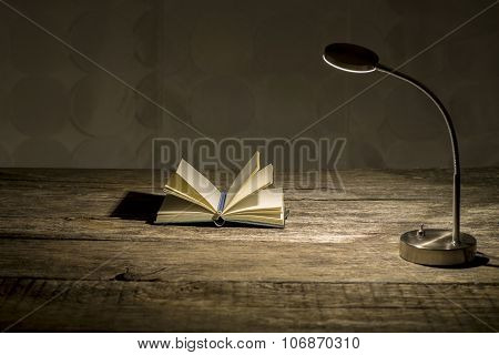 Rustic Wooden Study Desk With Lit Table Lamp And Open Notebook