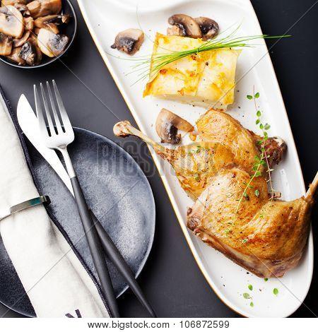 Duck legs confit with potato gratin, mushroom sauce . Restaurant serving.