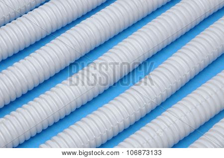 White plastic corrugated pipes on blue background