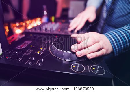 Club DJ playing mixing music on vinyl turntable