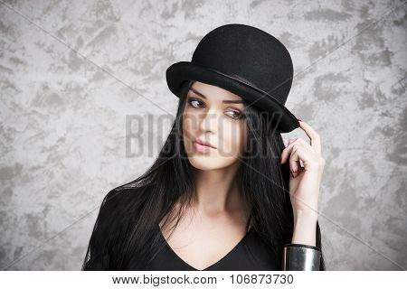 Portrait Of A Beautiful Young Woman In A Black Dress And Bowler Hat