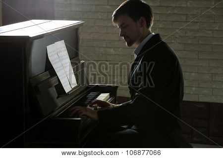 Musician plays piano in dark studio