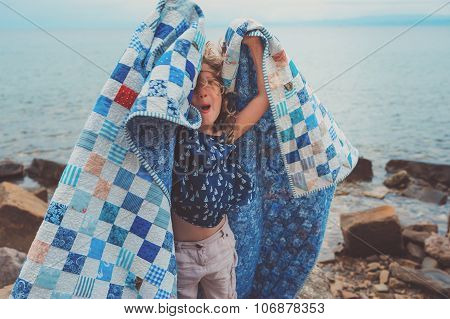 happy child girl at sea side in cozy quilt blanket
