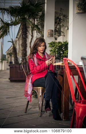 fashionable young woman sit in outdoor cafe make sending message on smart phone,wearing red coat and cashmere scarf