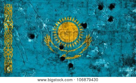 Kazakhstan flag painted on metal texture with bullet holes