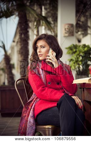 fashionable young woman sit in outdoor cafe make a phone call, wearing red coat and cashmere scarf