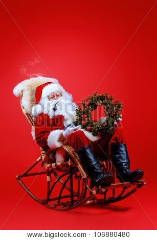 Good old Santa Claus sitting in a rocking chair over red background. Christmas.